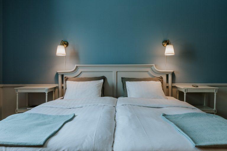Sovrum med två sängar och blåmålad vägg