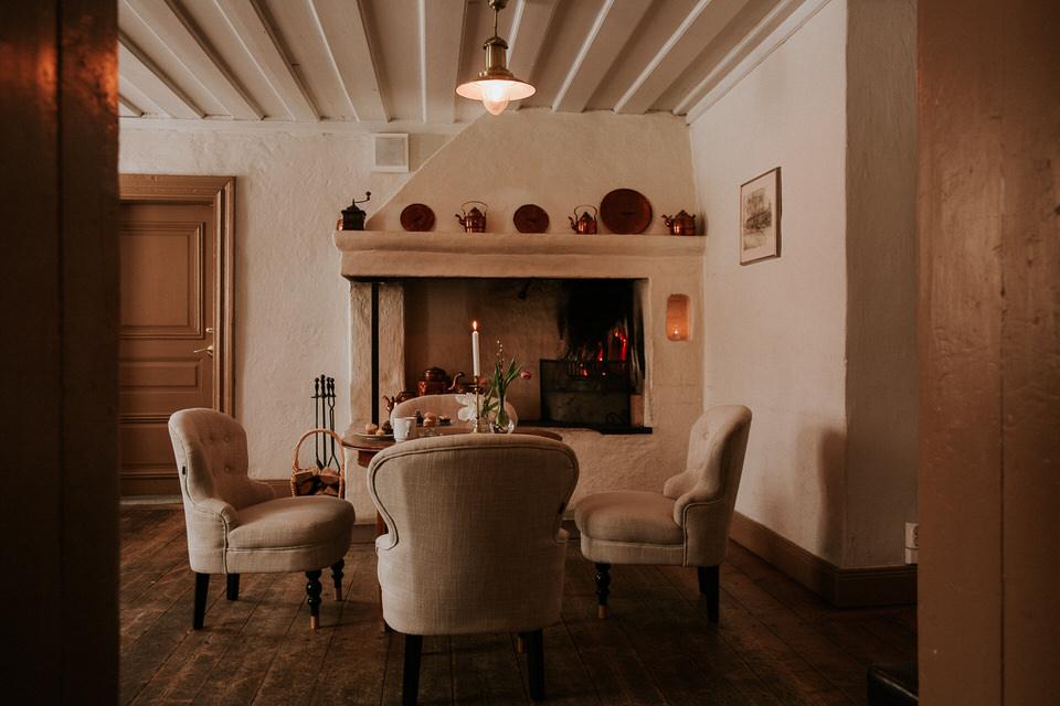 Öppen spis och fåtöljer i ett mysigt sällskapsrum på Schenströmska herrgården