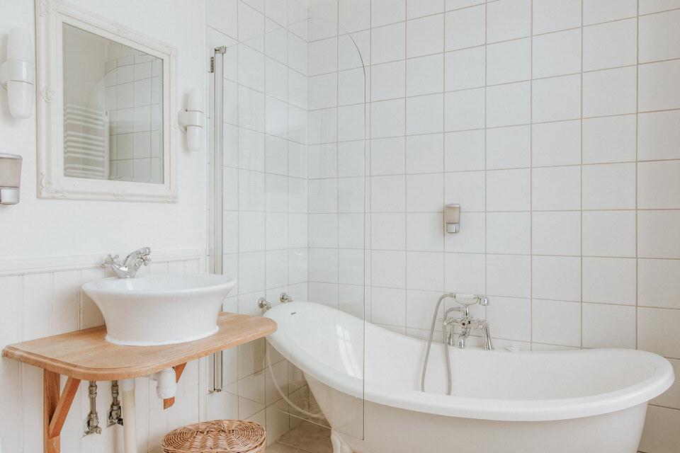Helkaklat badrum i vitt med badkar och handfat i ett av rummen på Schenströmska Herrgården
