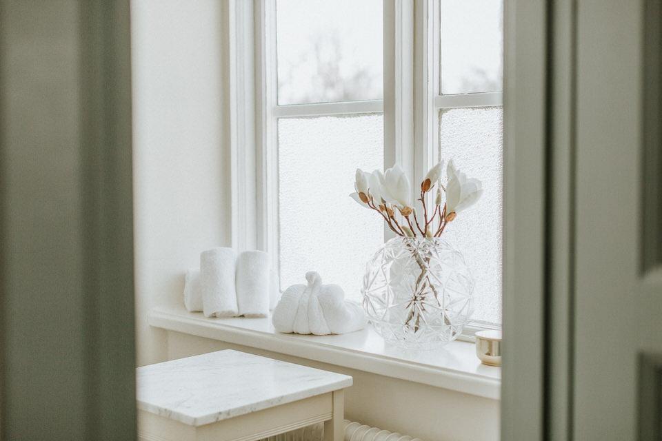 Inredning och vikta handdukar i fönstret i ett av rummen på Schenströmska herrgården
