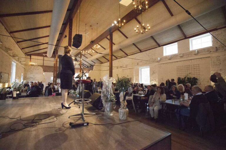 Kvinna står på scenen under ett event på Schenströmska herrgården