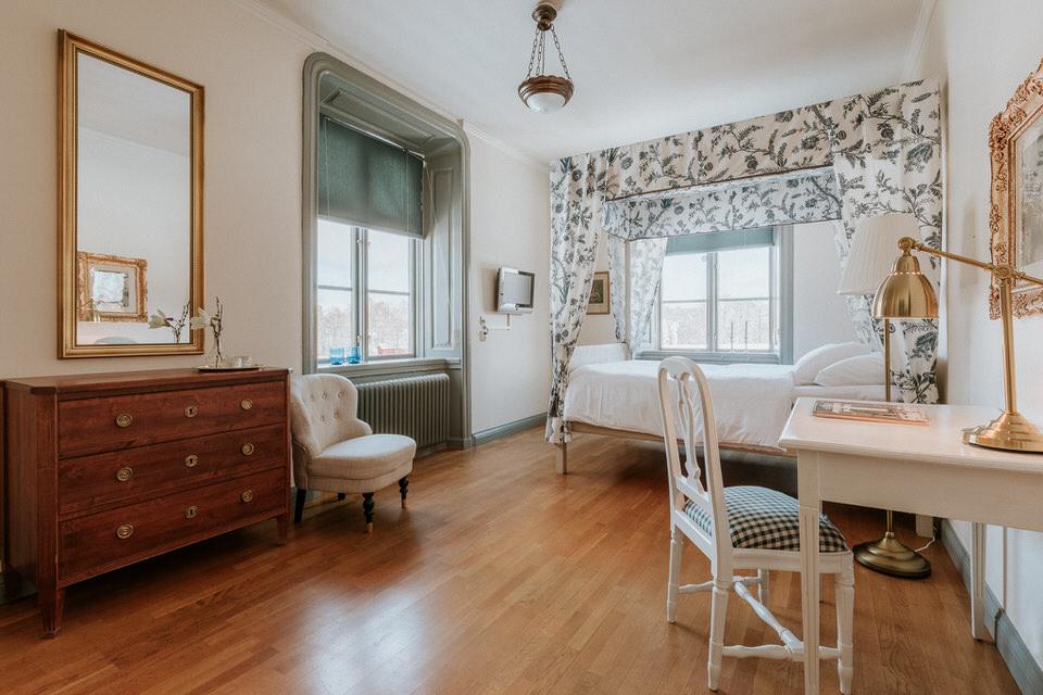 Rum med sänghimmel, skrivbord och stor spegel på Schenströmska herrgården