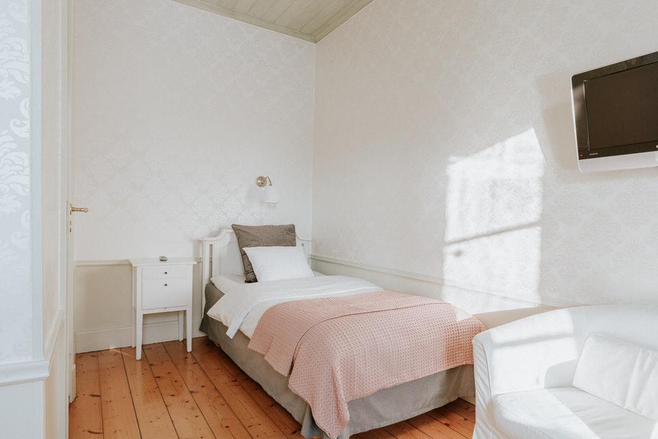 Enkelsäng i rum med tv och fåtölj på Schenströmska herrgården