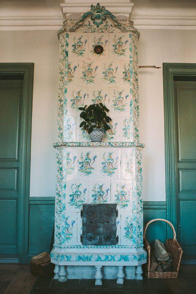 Vacker, gammal kakelugn med dekorativt mönster i matsalen